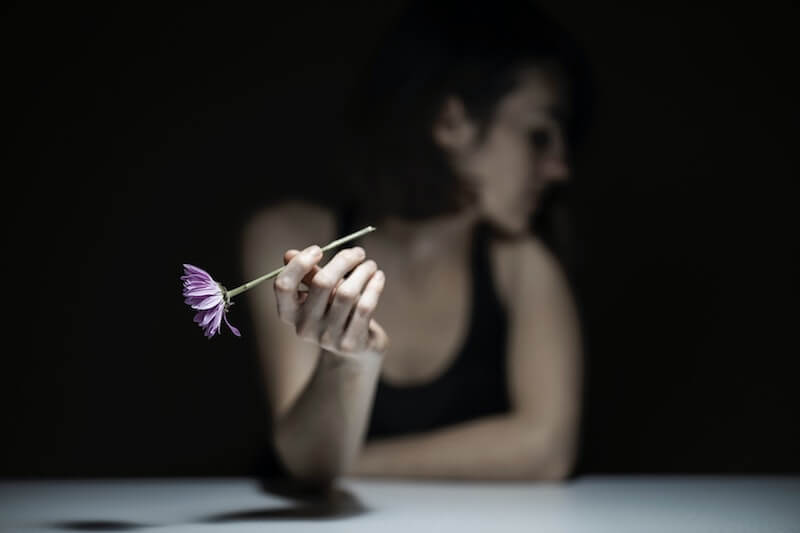 Depressed woman holding a flower